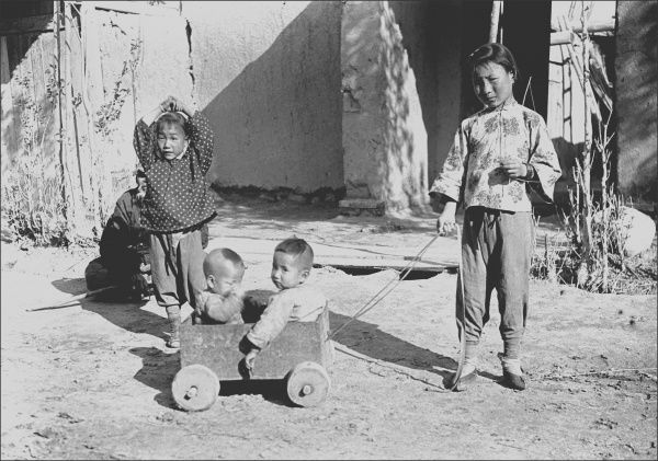 Four children in Kashgar, western China. Two small boys sit in a cart on wheels, pulled by an older girl