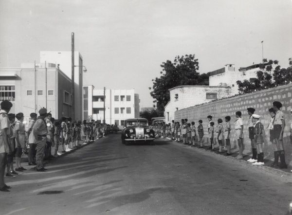 Yemeni Scouts line the street as a large black car carrying the Chief Scout of Aden, His Excellency the High Commission, Sir Richard Turnbull, G.C.M.G. arrives to open the new Headquarters of the South Arabian Boy Scouts Association in Aden, Yemen