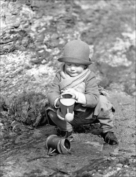 A young child playing with two small watering cans. Photograph by Ralph Ponsonby Watts