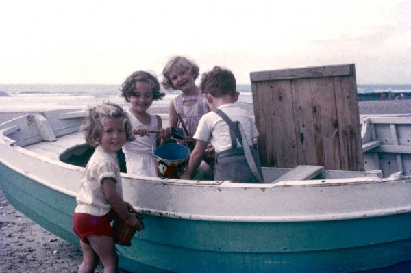 Four children -- three girls and a boy -- on a beach, playing with a boat. They are all happy and smiling