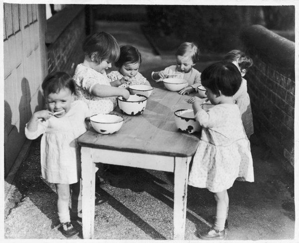 Children at the National Adoption Society's home in Harlesden brush their teeth standing at a wooden table using bowls