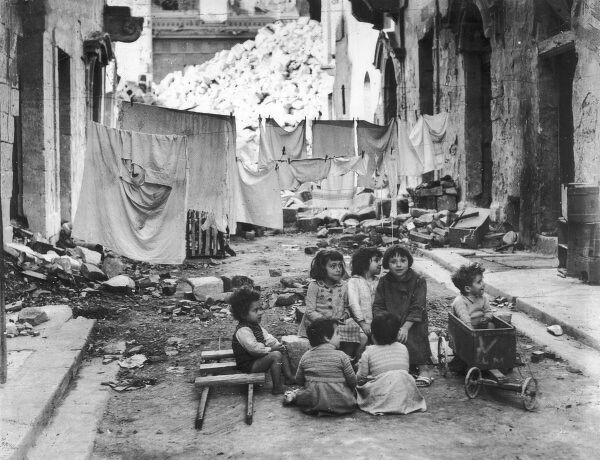 A group of children play in a street in Malta, under the hanging lines of washing, the damage and rubble attesting to weeks of attacks on the Island. During World War II, Malta played an important role owing to its proximity to Axis shipping lanes