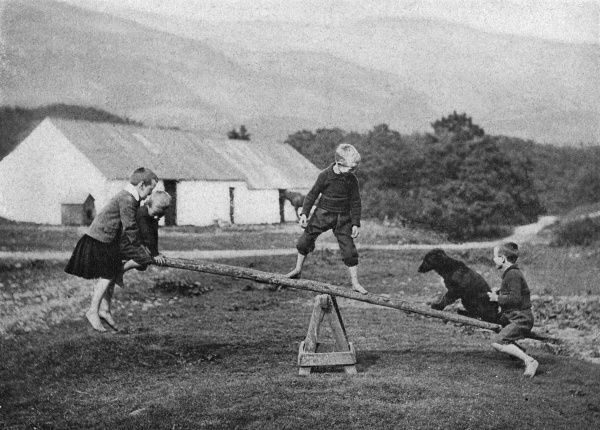 Children and a dog play on a seesaw in Scotland, showing the strong bond and trust man has in dogs. Date: 20th century