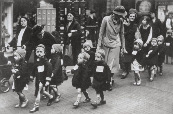 The photograph shows a group of children from Sherborne Nursey School in Kentish Town being evacuated during the Blitz