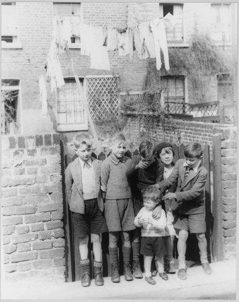 Six children stand at the garden gate of a terraced house