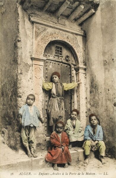 Five children sitting and standing beside an ornate doorway - Algeria