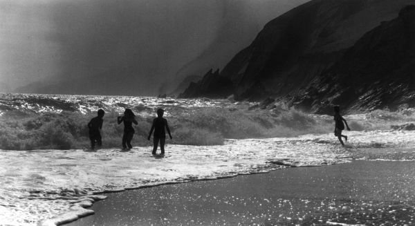 Children play in the waves on an Irish beach. Date: 1963