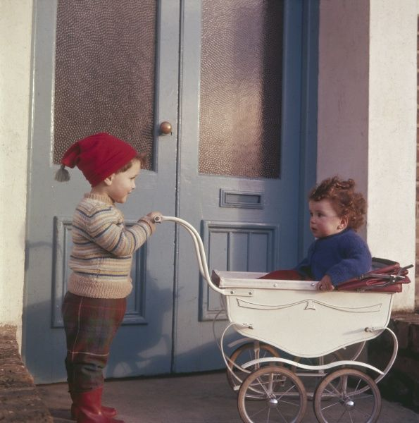 A little boy in a red bobble hat and red wellington boots pushes his young brother (or sister) in a pram