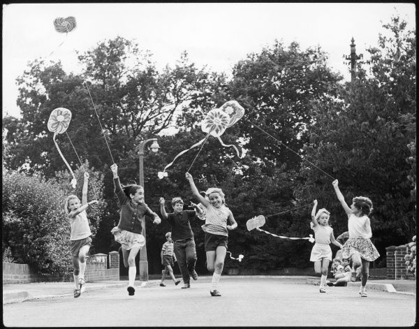 Children race down the street with kites on a windy day, in Horley, Surrey