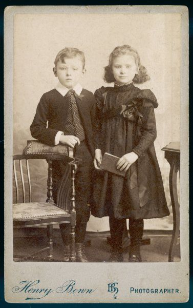 Boy: Knickerbocker suit with open jacket & rounded front borders, spotted waistcoat & Eton collar. Girl: high necked dress with yoke, tight sleeves & epaulettes, sash & rossette