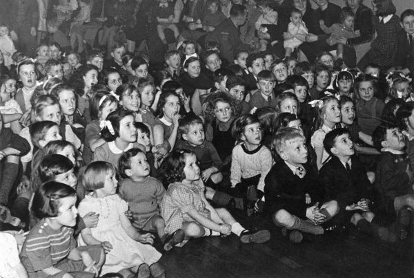 A large group of children sitting on the floor, watching some kind of entertainment. Some are smiling, others looking up in shock or wonder, or just concentrating hard. A few adults are sitting on chairs on the right with the younger children
