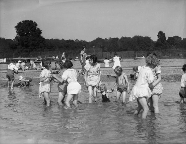 Children playing in a public paddling pool, the little girls with their dresses tucked into their knickers to stop them getting wet!