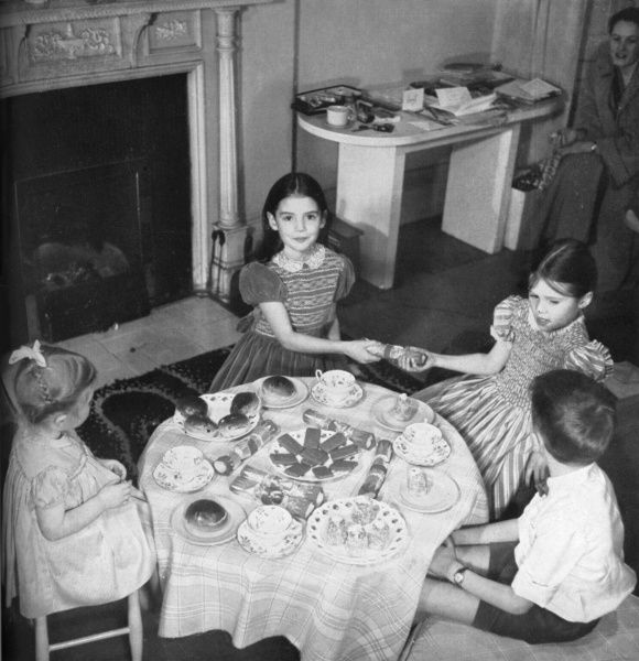 Four children enjoy a charming (if a little sparse) looking Christmas tea party. The girls are wearing smocked party dresses by Lindsay Maid and two of them pull crackers while their companions look on politely. Date: 1953