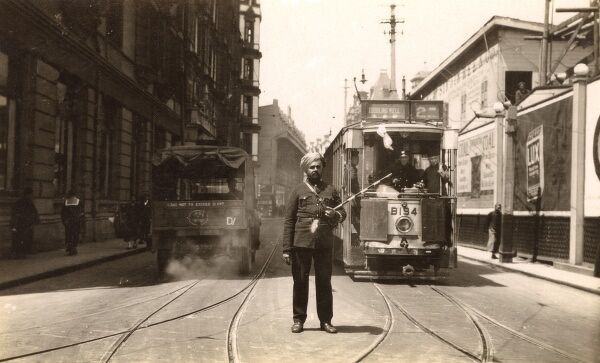China - Shanghai - Street scene in the International Settlement with tram and British Colonial Indian Policeman/soldier (?), who is trying to direct the various forms of transport using the road! (including an American jeep) Date: circa 1935