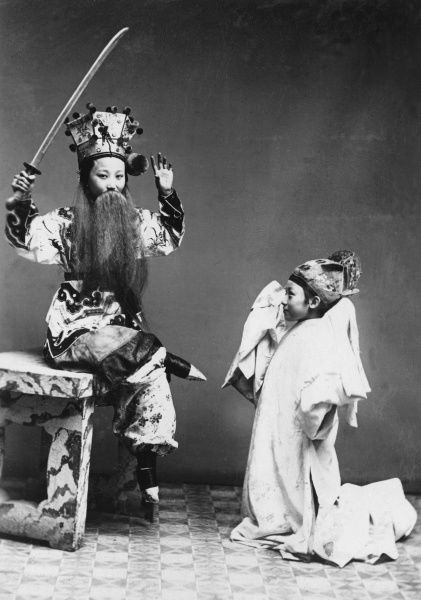 Chinese actors during a performance. The caption describes the principal performer as an actress - is she in drag ?