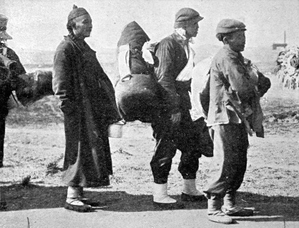 Photograph showing Chinese boys and an old Chinese man in traditional dress with long jacket, cap and pigtail, in the process of emigrating from South Africa, 1907