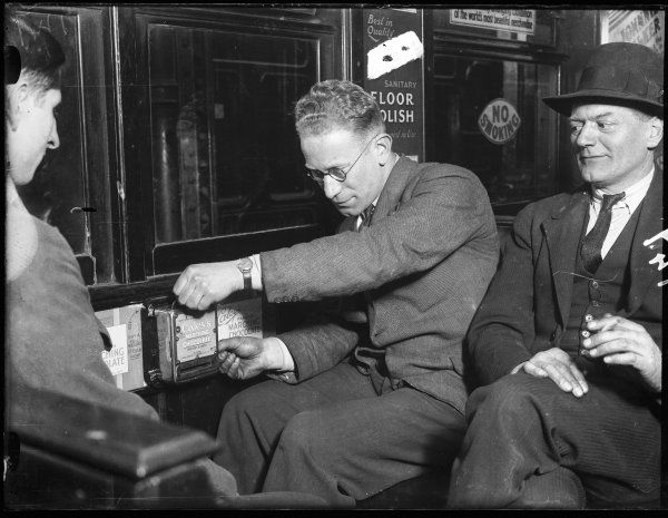 Other passengers watch as a man tries to work out how to use an automatic slot machine vending 'Caley's famous Marching Chocolate', inside a metropolitan railway carriage