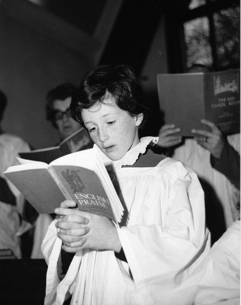 A choirboy singing in a church choir at Salfords Church, Horley, Surrey. He is holding a book entitled 'English Praise', though other choristers are using 'The Red Carol Book&#39