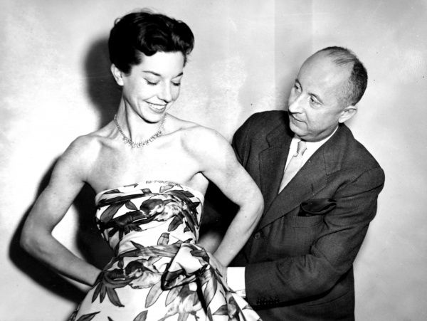 Photograph showing Christian Dior (1905-1957), the French couturier, draping a length of material around the model, Dorothy Emms, London, November 1952