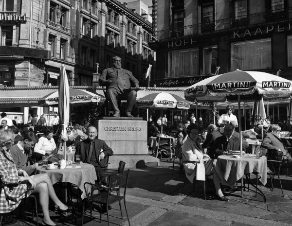 Memorial statue of Norwegian naturalist painter, author and journalist CHRISTIAN KROHG (1852 - 1925), surrounded by tourists enjoying a drink at an open air cafe, Oslo, Norway Date: late 1960s
