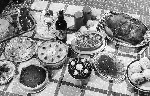 Wonderful assorted Christmas foods on a table, including bean stew, peas pudding, roast duck, rabbit jelly mould, rock cakes, meringues, trifle, souffle, Christmas cake, etc