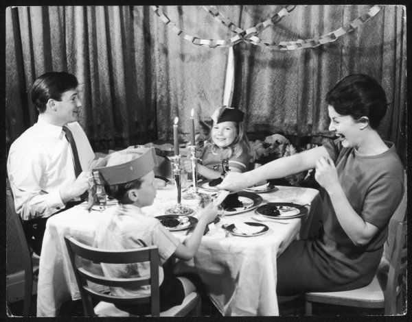 Mother squeals with laughter as she pulls a cracker with her son after Christmas dinner. Father looks at his daughter, who grins at the camera.. Merry Christmas!