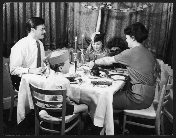 A family enjoy their Christmas pudding on Christmas Day. Date: 1960s