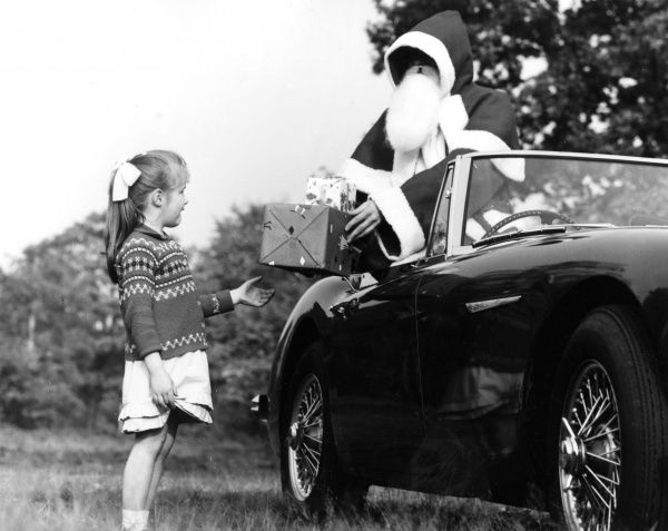A little girl is given a present from Father Christmas who prefers a sports car to a sleigh any day Date: 1960s