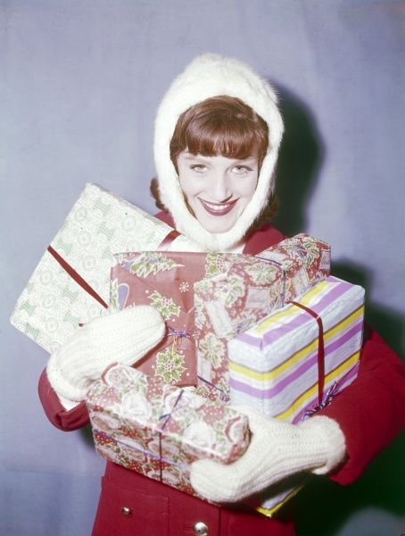 A woman wearing a white fur hat carries a pile of Christmas presents. Date: 1960s