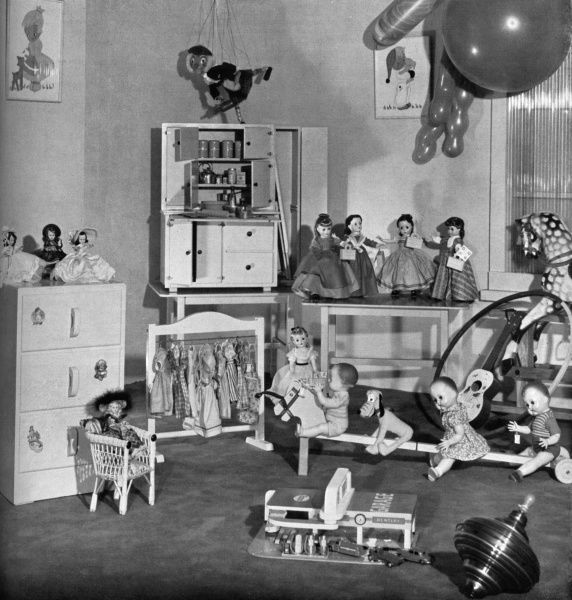 An array of exciting toys for potential Christmas present ideas in 1953, including a wicker chair, several dolls including a set of 'Little Women' dolls, a puppet, a toy garage, a kitchen cupboard complete with ironing board, a rocking horse