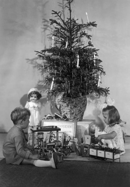 A little boy and girl sit underneath the Christmas tree with all their new toys