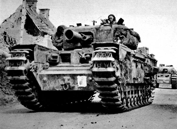 Photograph showing a Churchill AVRE (Armoured Vehicle Royal Engineers) tank moving up to the front, France, 1944