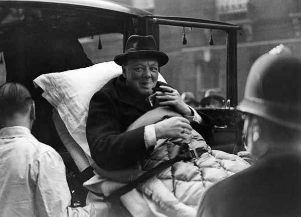 Winston Churchill (1874-1965), English politician, having a cheeky puff on his cigar whilst being stretchered from his London flat to a West End nursing home via ambulance, having been taken ill with paratyphoid. Date: 1932