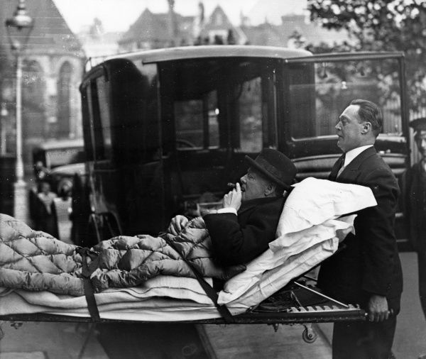 Profile view of Winston Churchill (1874-1965), English politician, having a cheeky puff on his cigar whilst being stretchered from his London flat to a West End nursing home via ambulance, having been taken ill with paratyphoid. Date: 1932