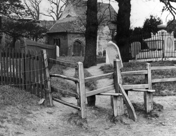 The typical wooden stile of a churchyard in Chingford, Essex, England. Date: 1930s