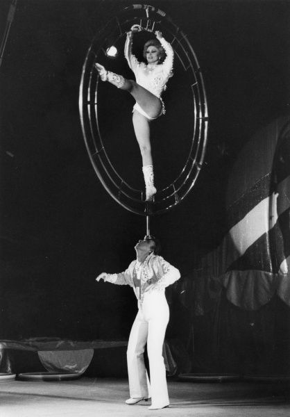 At the Moscow State Circus, a male acrobat skilfully balances a female acrobat on his forehead. Presumably she is going to spin around in the strange metal contraption!