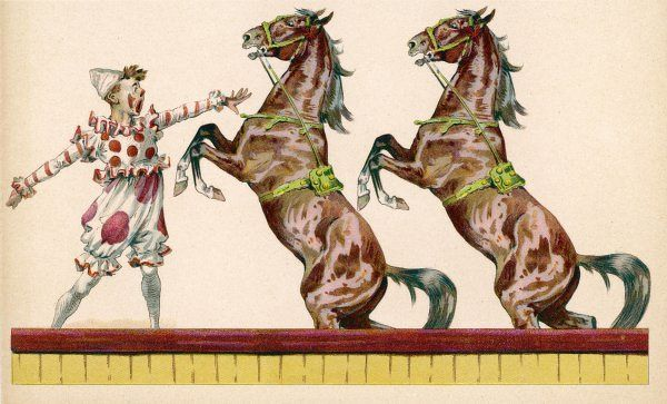Two horses perform at the circus clown's bidding