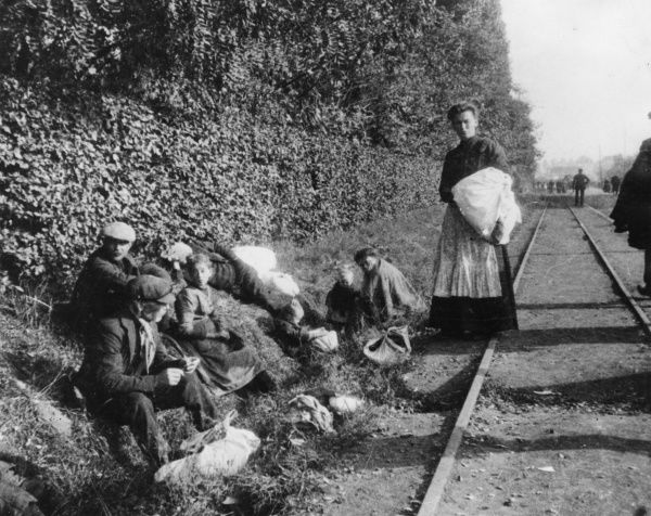 Civilian refugees resting at the side of a rail track near Ghent, Belgium, during the First World War. Date: 9 October 1914