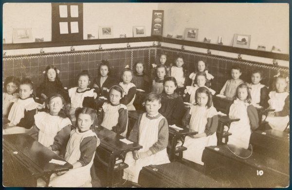 A classroom of girls in a girls' school. They are all wearing white smocks