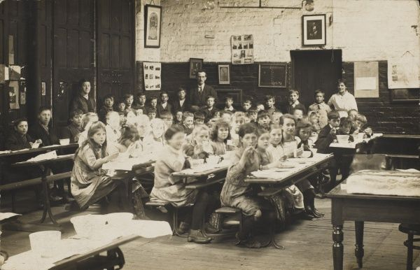 A classroom scene, with pupils eating their midday meal at their desks, at an unidentified mixed school