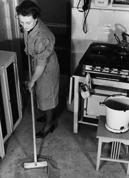 An ingenious housewife saves her back by cleaning her kitchen floor with a cloth and a sweeping brush. Date: 1940s