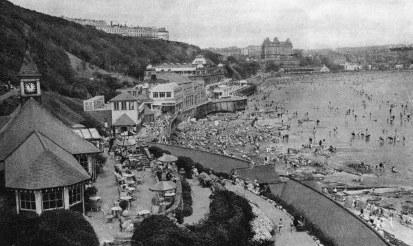 The South Cliff Gardens Cafe (known today as the Clock Cafe), with a view of the beach below, at Scarborough, North Yorkshire. The sea and beach are crowded, and the Grand Hotel can be seen on the distant horizon. Date: 1920s