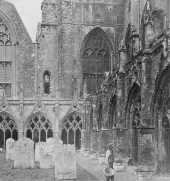 View of the Cloister Graveyard and part of Canterbury Cathedral, with a man at work