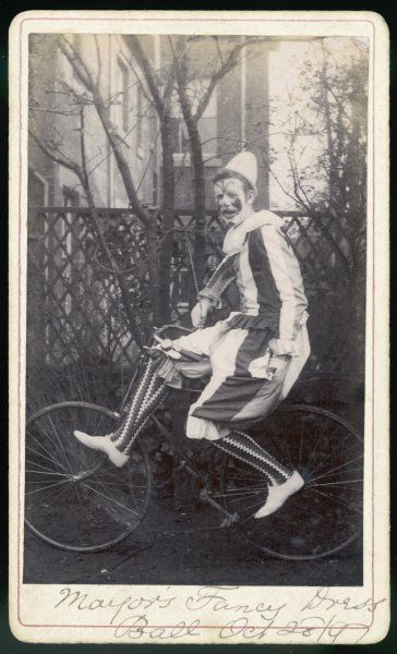 Harry, a guest of the Mayor's Fancy Dress Ball poses in his costume,(that of a clown), on a bicycle in his back garden
