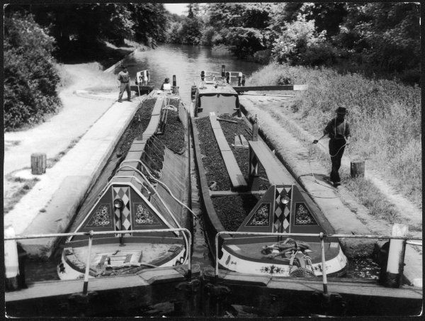A pair of laden narrow boats, with their cargoes of coal, passing through a lock on the Grand Union Canal near Watford, Hertfordshire, England