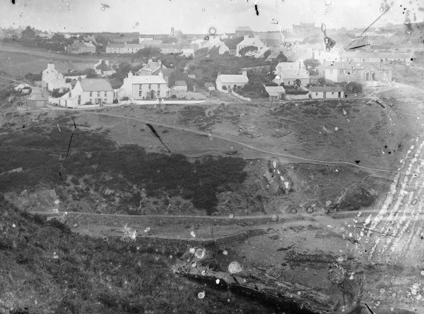 View of a coastal village and port in Pembrokeshire, South Wales, with a wrecked boat disintegrating at the bottom of the picture