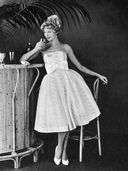 A woman wearing a white lace cocktail dress by Bijou, enjoys a cocktail at what is now considered quite a kitsch, Tiki-style bar