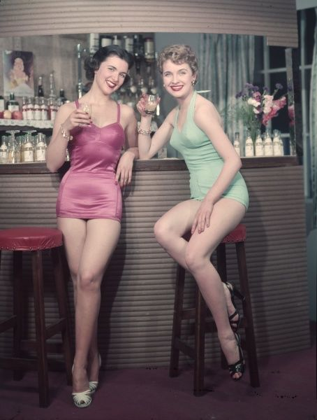 A blonde perched on a bar stool & a brunette leaning against the bar sip refreshing drinks while wearing one piece bathing costumes & strappy high-heeled sandals