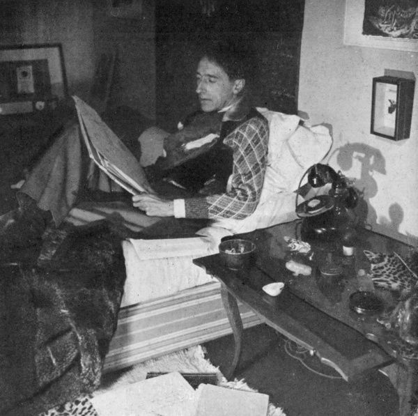 JEAN COCTEAU French writer, artist and film maker, reading in bed in 1941