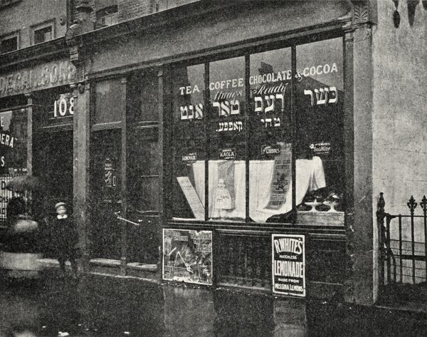 A coffee house near Jubilee Street in the East End of London. Its window contains both English and Hebrew text. There are advertisements for R. White's Lemonade and Kaola